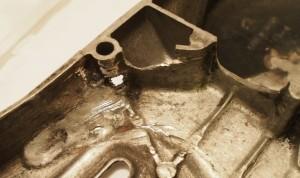 Täällä on joskus rysähtänyt; hitsaus, reikä ruuvinpaikan kyljessä, lohjennut pala magneeton suojan seinästä.