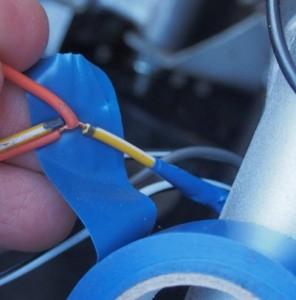Molemmista jakopisteistä irroitettiin Y/W -lenkit. Etummaiseen kiinnitettiin irroituksen jälkeen oranssi takaisin. Molemmat suojattiin teipillä (tässä sininen teippi). Tämä johtolinja on 12 VDC tasasähkölinja.